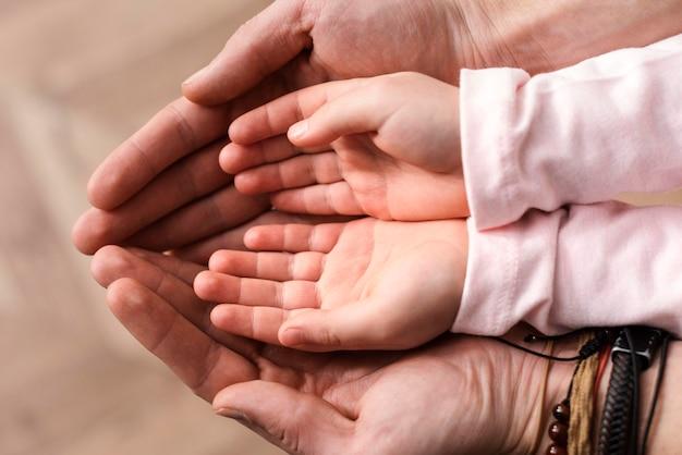 Vista superior de la niña poniendo sus manos en las manos del padre