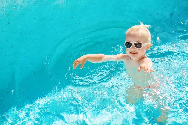 Vista superior de la niña que nada en la piscina con agua azul.