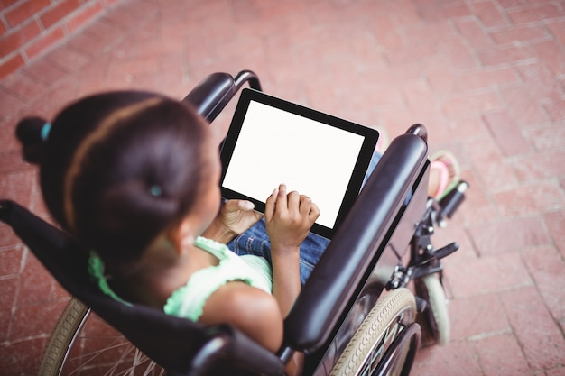 Vista superior de una niña sentada en una silla de ruedas