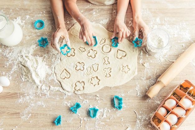 Vista superior de la niña y su madre preparando galletas.