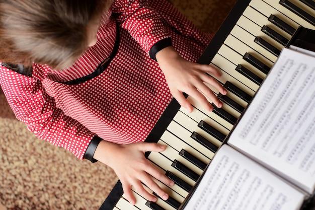Vista superior de una niña tocando el piano en casa