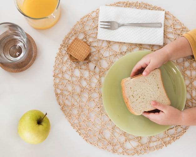 Vista superior niño desayunando