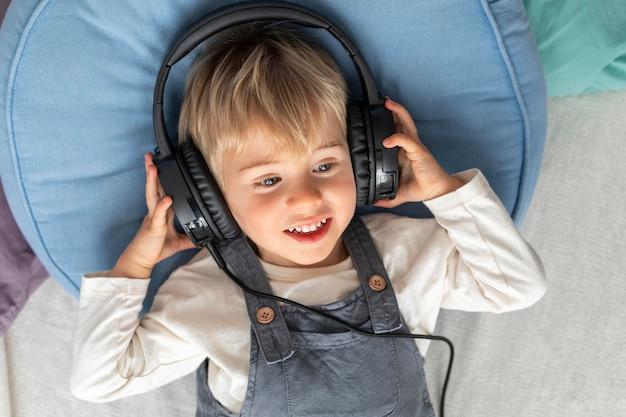 Vista superior niño escuchando música en auriculares