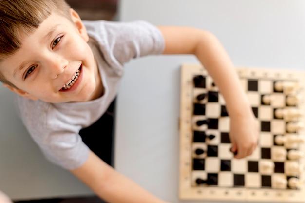 Vista superior niño con juego de ajedrez
