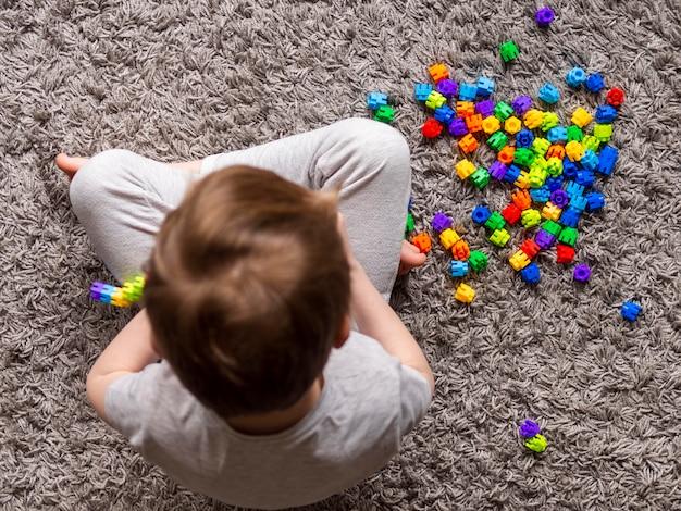 Vista superior niño jugando con colorido juego