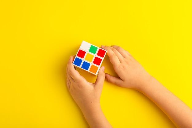 Vista superior niño jugando con cubo de rubics en superficie amarilla