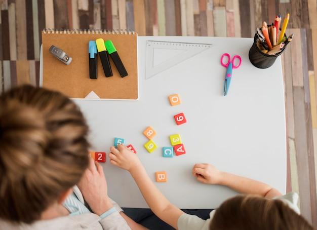 Vista superior del niño y el tutor aprendiendo sobre números y letras