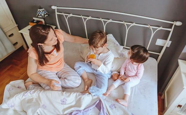 Vista superior de niños felices desayunando en la cama con su madre en una mañana relajada. concepto de tiempo de ocio familiar de fin de semana.