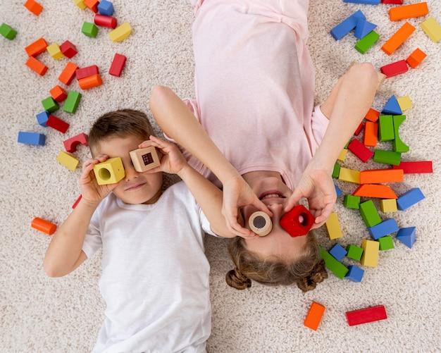 Vista superior de niños no binarios jugando con un juego colorido