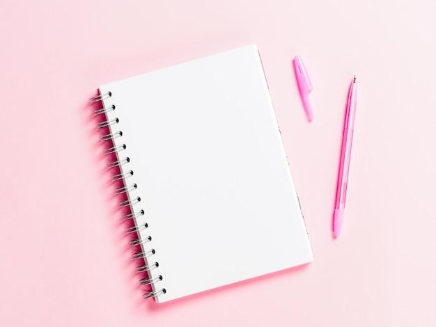 Vista superior de la nota en blanco con lápiz sobre fondo rosa