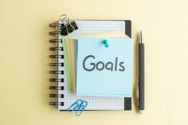 Vista superior de la nota escrita de los objetivos junto con pequeñas notas de papel de colores sobre una superficie clara, color escolar, trabajo de oficina, cuaderno de trabajo