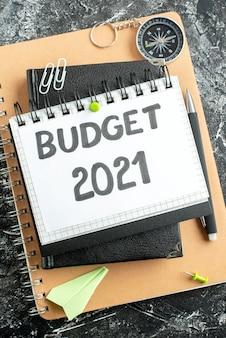 Vista superior de la nota presupuestaria en el bloc de notas con bolígrafo sobre la superficie oscura de color estudiante universitario dinero escolar banco de trabajo empresarial