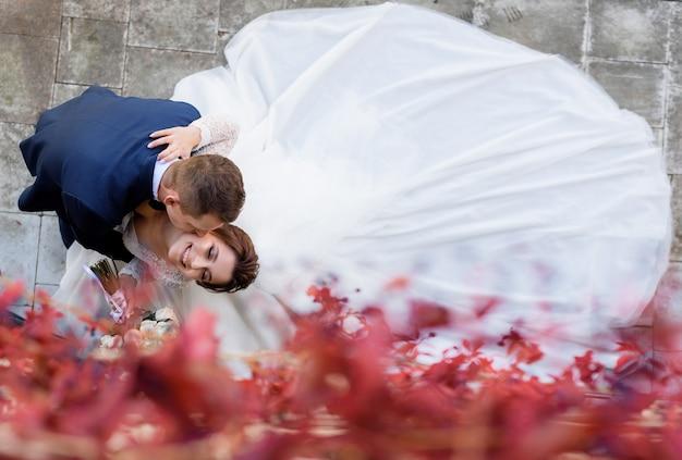Vista superior de la novia y el novio sonríe besándose en la mejilla, feliz matrimonio
