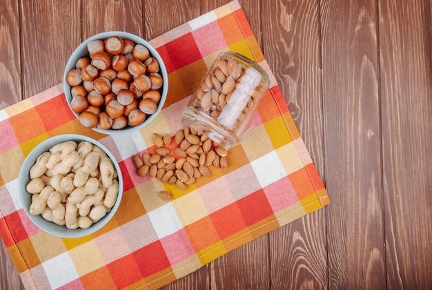 Vista superior de nueces, cacahuetes, avellanas en cuencos y almendras esparcidas desde un frasco de vidrio sobre una servilleta de tela escocesa sobre fondo de madera con espacio de copia