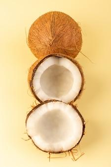 Una vista superior de nueces de coco en rodajas lechosas frescas suaves aisladas en color crema