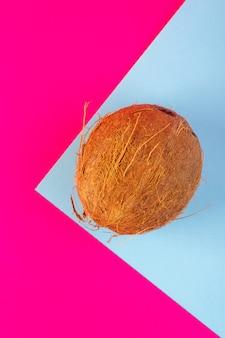 Una vista superior de nueces de coco en rodajas y todo dulce lechoso fresco aislado en el rosa y el azul helado