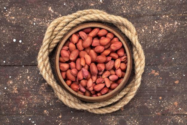 Vista superior de nueces crudas marrones dentro de un tazón redondo con cuerdas en sal de bocadillo de nuez marrón y nuez