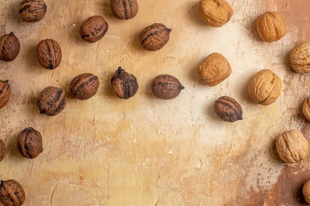 Vista superior de nueces frescas forradas en un escritorio de madera