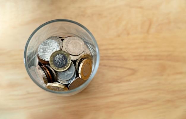 Vista superior nueva moneda de una libra esterlina británica y centavo y en botella de vidrio sobre mesa de madera