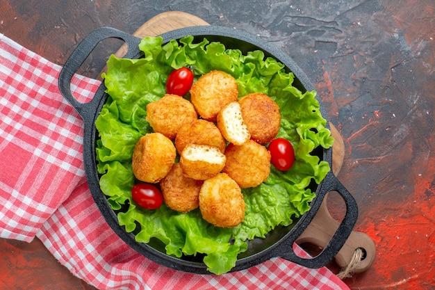 Vista superior de nuggets de pollo, lechuga, tomates cherry en una sartén en la tabla de cortar en la pared de color rojo oscuro.