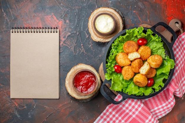 Vista superior de nuggets de pollo, tomates cherry, lechuga en sartén, cuencos de salsa en el cuaderno de tableros de madera en la pared de color rojo oscuro