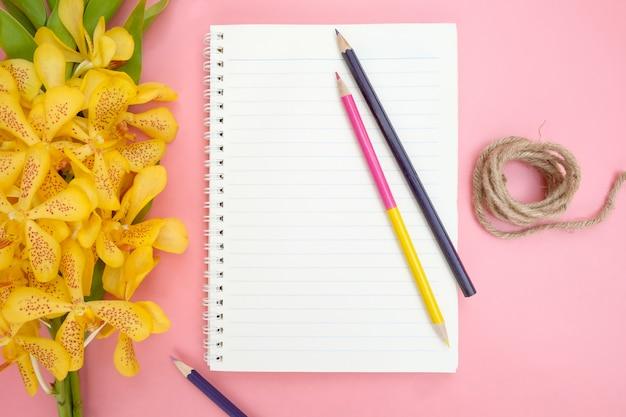 Vista superior o plano de papel de cuaderno abierto, flores de orquídeas amarillas, lápices de colores y cuerda natural sobre fondo rosa.