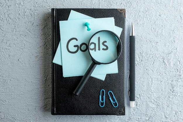 Vista superior de los objetivos nota escrita con el bloc de notas y un bolígrafo en la superficie blanca oficina de trabajo cuaderno escolar color negocio universitario