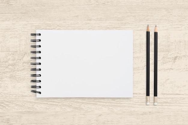 Vista superior del objeto de cuaderno en blanco y lápiz sobre textura de madera.