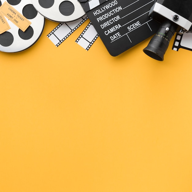 Vista superior de objetos de cine sobre fondo amarillo con espacio de copia