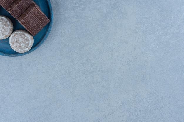 Vista superior de obleas de chocolate con galleta en placa de madera azul.