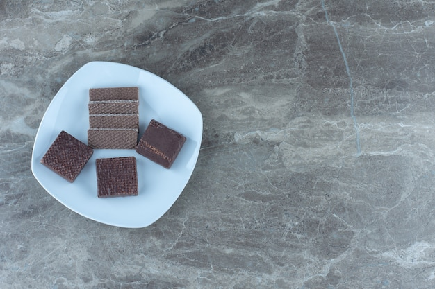 Vista superior de obleas en plato blanco sobre mesa gris.