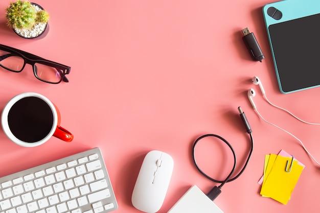 Vista superior de la oficina de escritorio de color rosa pastel con espacio de copia para ingresar el texto.