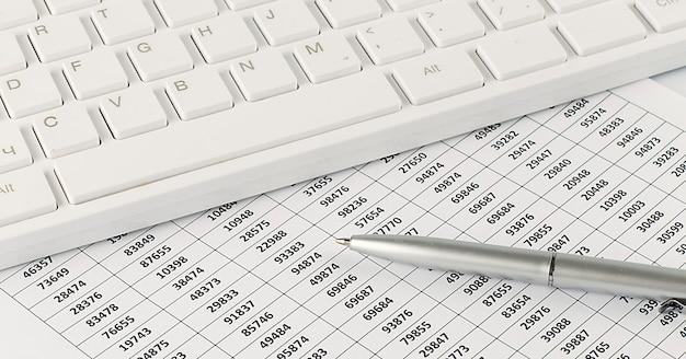 Vista superior de la oficina de finanzas comerciales y el concepto de marketing en el escritorio de mesa blanca con teclado y documento gráfico