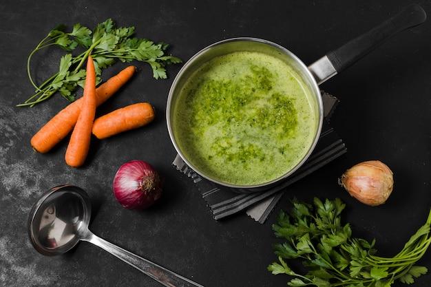 Vista superior de la olla de sopa con zanahorias y cebolla