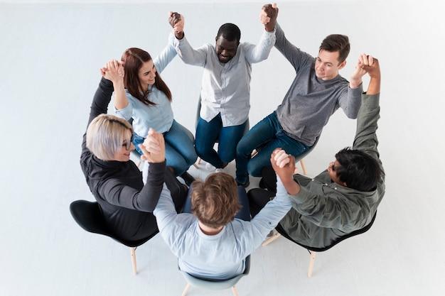 Vista superior de pacientes de rehabilitación levantando las manos