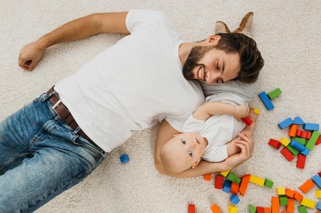 Vista superior del padre y el bebé en casa con juguetes.