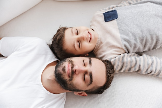 Vista superior de un padre sonriente y su hijo acostado en un sofá en casa