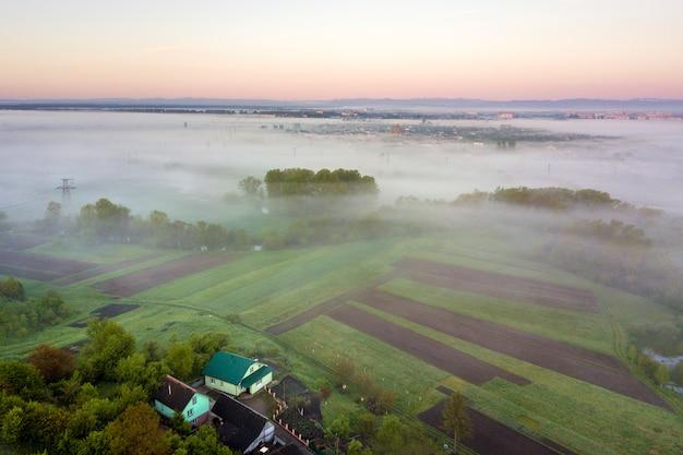 Vista superior del paisaje rural en día soleado de primavera. cultive cabañas, casas y graneros en campos verdes y negros. fotografía de drones.