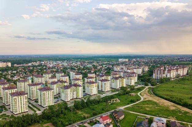Vista superior del paisaje urbano de la ciudad en desarrollo con altos edificios de apartamentos y casas de los suburbios. drone fotografía aérea.