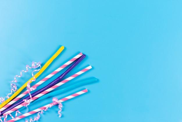 Una vista superior de pajitas de colores largos y pegajosos aislados en azul, beber jugo de color frío