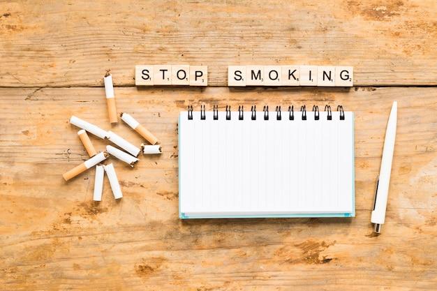 Vista superior palabra con cigarros y cuaderno