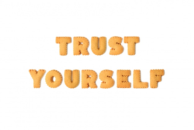 La vista superior de la palabra confíe en usted mismo deletreada con las galletas formadas alfabeto aisladas en el fondo blanco