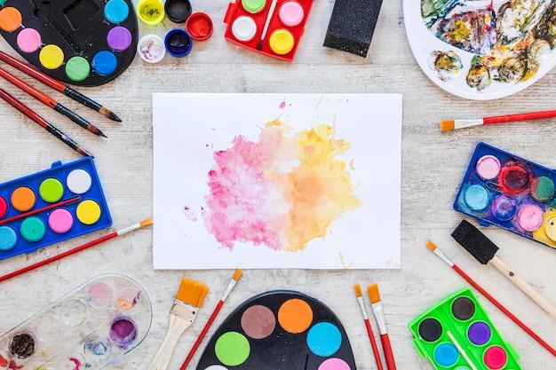 Vista superior de la paleta de la bandeja de color y salpicaduras sobre papel
