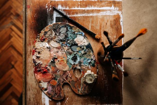 Vista superior de la paleta y de los cepillos del artista en un fondo de madera.