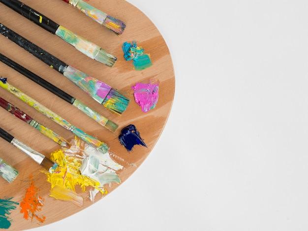 Vista superior de la paleta con pintura y pinceles.