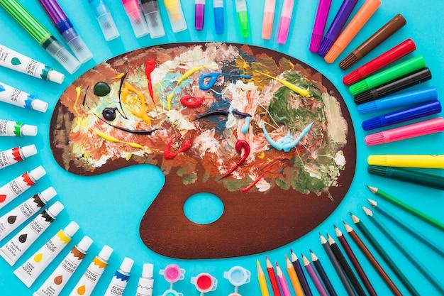 Vista superior paleta de pintura rodeada por elementos de pintura