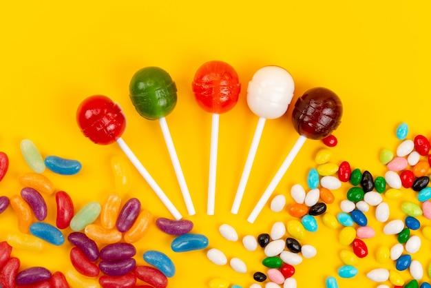 Una vista superior de paletas y caramelos de color dulce aislado en amarillo, confitería dulce de azúcar