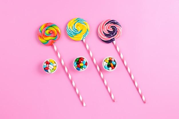 Una vista superior de paletas dulces de colores en los palitos de azúcar de color rosa-blanco y caramelos multicolores en el arco iris de cumpleaños de fondo rosa