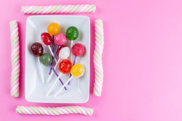 Una vista superior de paletas y malvaviscos dulces y pegajosos en confitería de color rosa, azúcar dulce