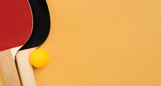 Vista superior de paletas de ping pong con pelota y espacio de copia